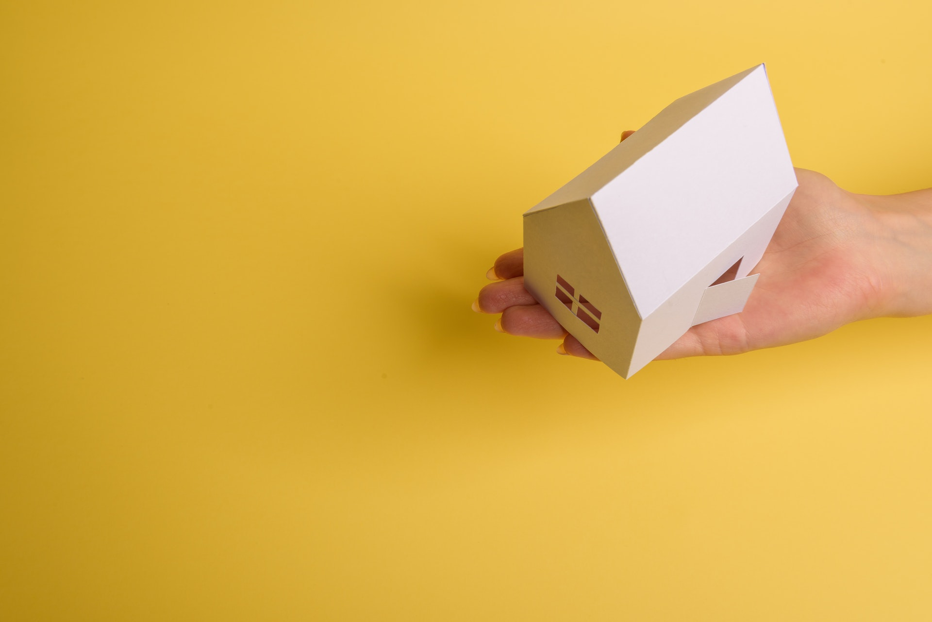 Hand holding a paper house