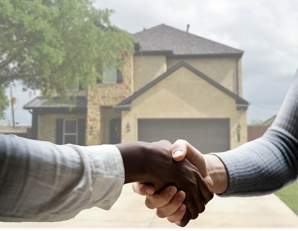 Two people shaking hands in front of house