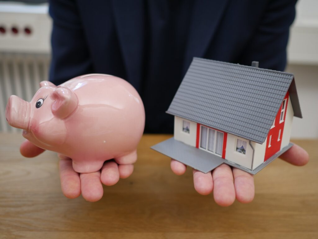 Person with a piggy bank and a small house model on the palms of his hands