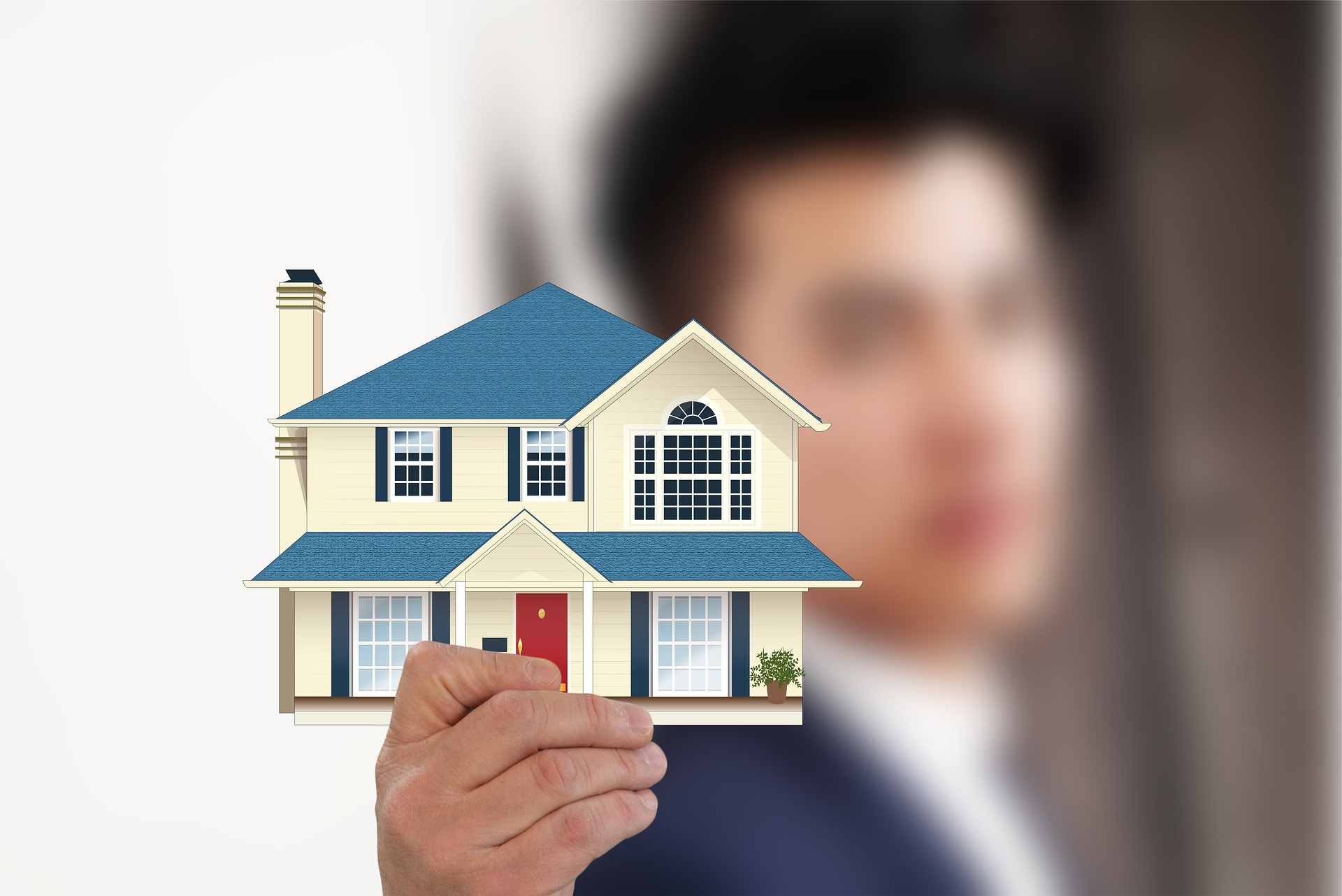 Selective focus of man holding a miniature house