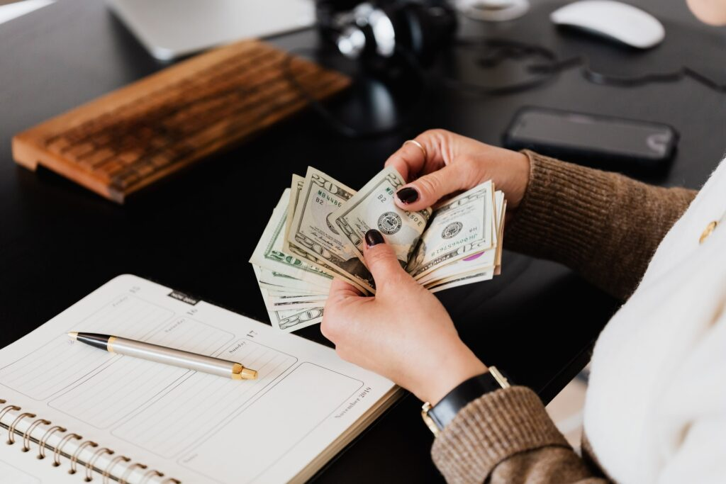 Woman counting money at office table