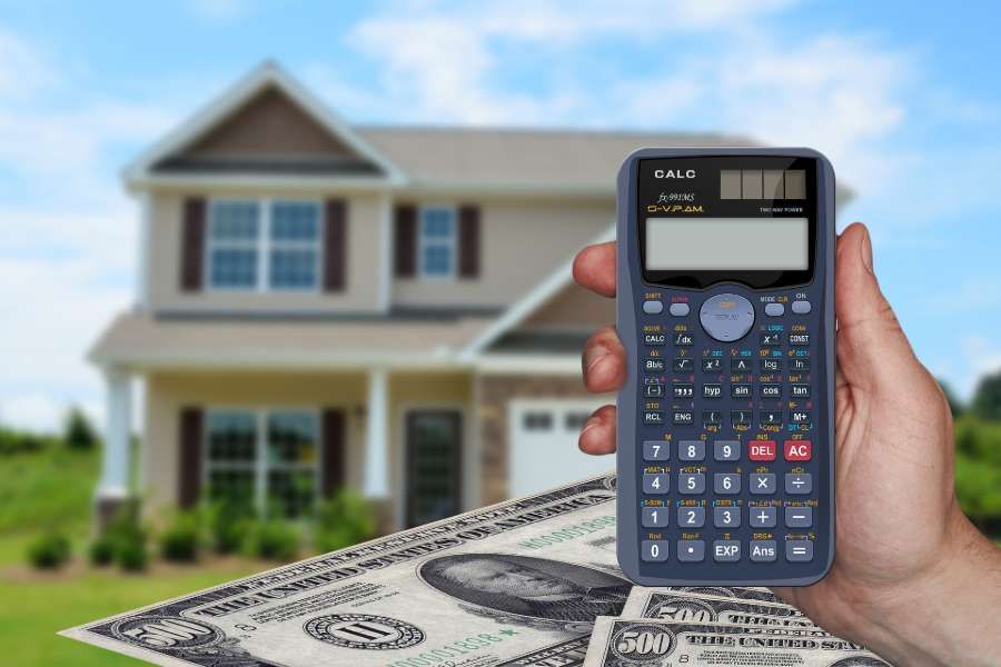 Hand holding a calculator to compute realtor fees and closing costs