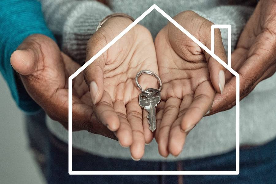 Two people holding a house key on their hands