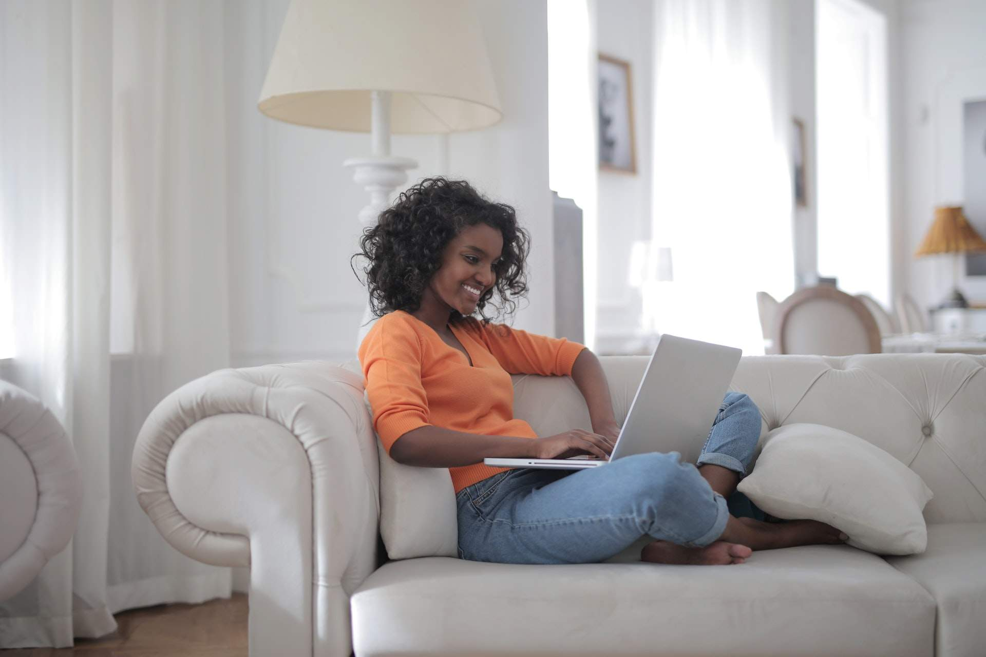 Woman sitting on a white couch while using a laptop
