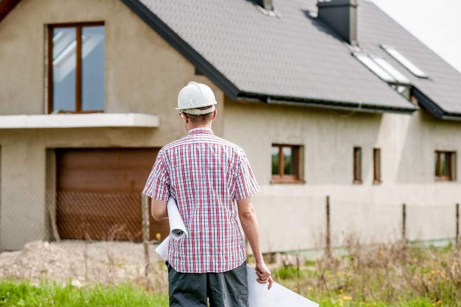 A contractor looking at an unfinished house construction