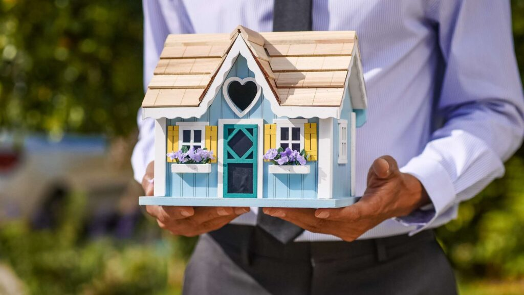 A real estate agent holding a miniature wooden house