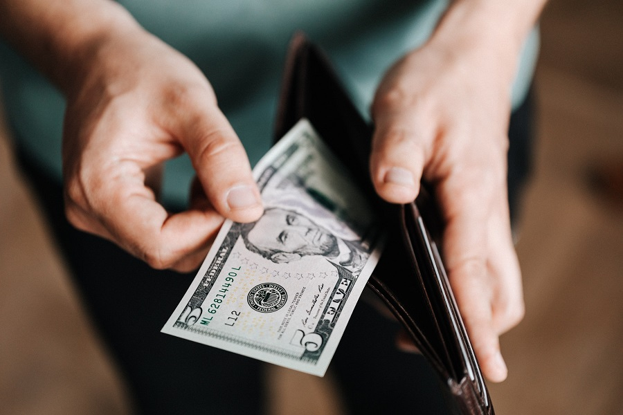 Person pulling out a bill from a wallet
